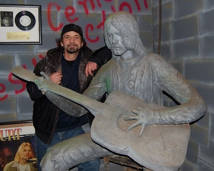 Nirvana's first drummer, Aaron Burckhard, poses with Randi Hubbard's statue of Kurt. The statue is now in Hubbs Muffler shop. Gillian G. Gaar/Examiner.com